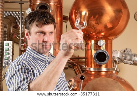 Man in front of distillery - copper - stock photo