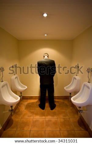 Man in front of urinal - stock photo