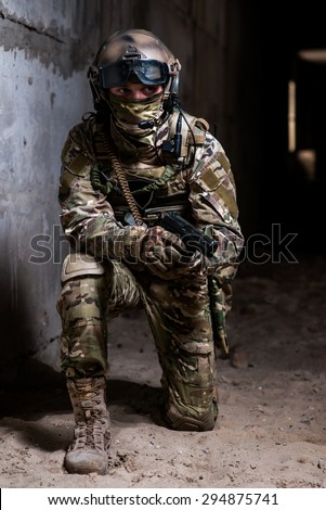 Man in full military ammunition stay on his knees and holding a gun