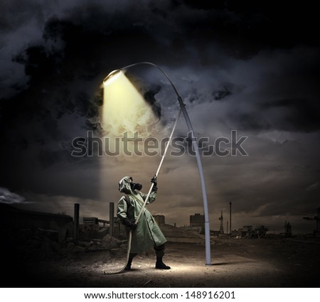 Man in gas mask and camouflage standing under street light