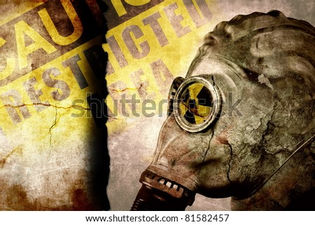 Man in gas mask on cracked wall, industrial grunge background, nuclear warning - stock photo