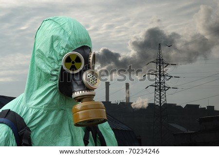man in gas mask on smoky industrial background with pipes and power line - stock photo
