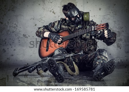 man in gas mask plays guitar - stock photo