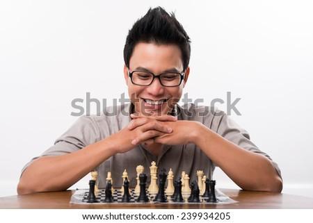 Man in glasses enjoying game of chess - stock photo