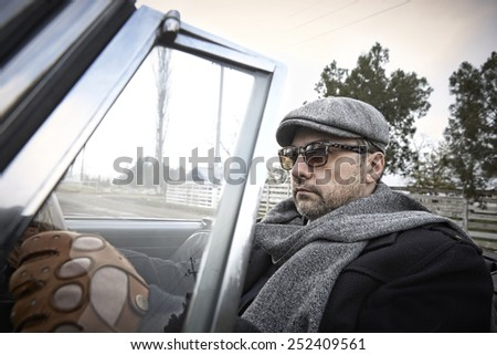 Man in glasses is driving vintage Lancia - stock photo