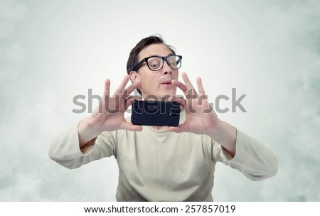 Man in glasses photographed by smartphone - stock photo