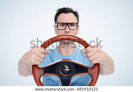 Man in glasses with wooden steering wheel, car driver concept