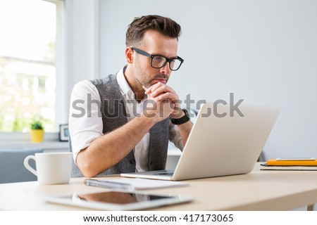 Man in glasses working on laptop from home