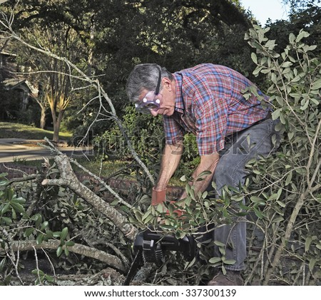Man in gloves and safety goggles cutting fallen branches and foliage debris after a storm