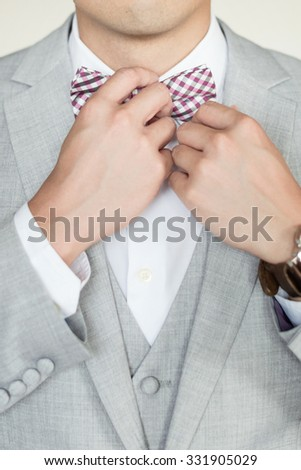 Man in gray striped jacket adjusting bow tie. Closeup.