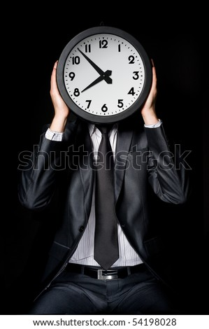 man in gray suit holding big clock covering his face - stock photo