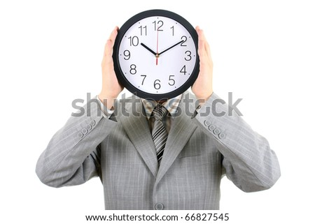 man in gray suit holding big clock covering his face over white - stock photo