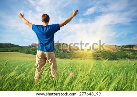 Man in green wheat meadow. Conceptual design. - stock photo