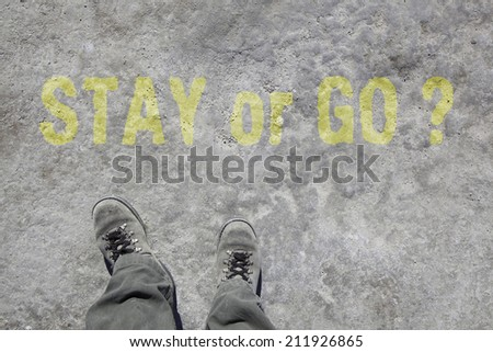 man in grey military boots and pants is looking down to his feet. On the stony ground is written Stay or go  in yellow color.  - stock photo
