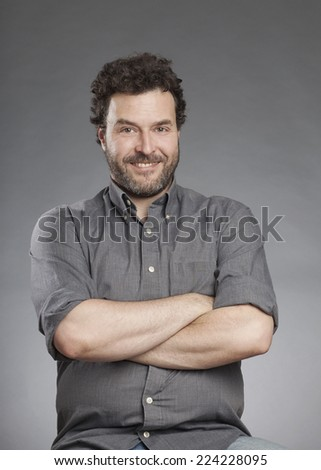 Man in grey shirt standing with arms crossed