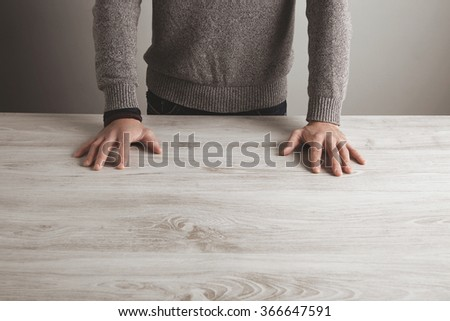 Man in grey sweater holds hands on blank white wooden table, isolated on simple wall