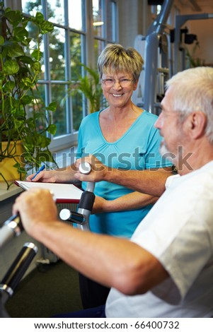 Man in gym using a rowing machine - stock photo