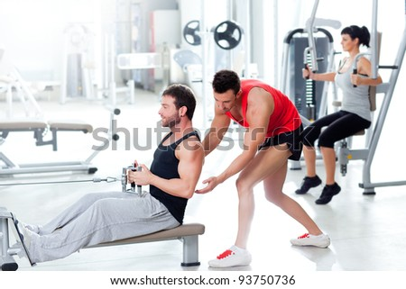 man in gym with personal trainer and fitness woman - stock photo