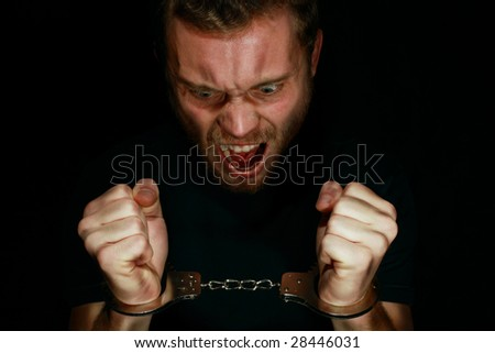 Man in handcuffs angry - stock photo