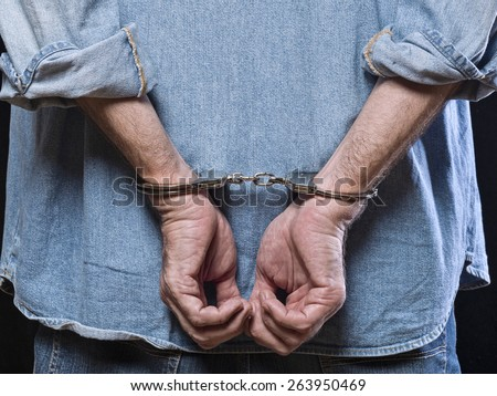 Man in handcuffs behind his back