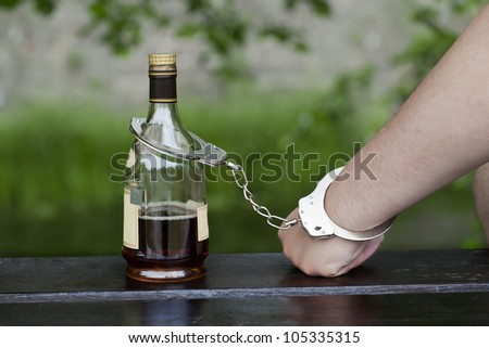 Man in handcuffs interconnected with a bottle of alcohol - stock photo