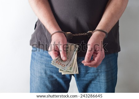 man in handcuffs is holding dollars - stock photo
