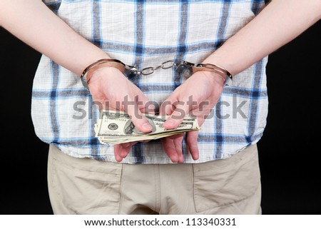 man in handcuffs is holding dollars, on black background