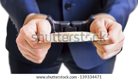 Man in handcuffs is holding money over white background - stock photo