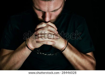 Man in handcuffs praying - stock photo