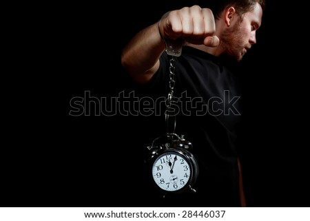 Man in handcuffs with a clock - stock photo