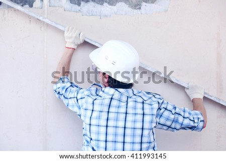 Man in hardhat aligns the walls with stucco  - stock photo