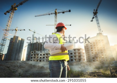 Man in hardhat and green jacket posing on building site at sunset - stock photo