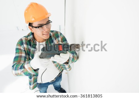 Man in hardhat making hole in wall with electric drill - stock photo