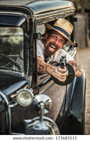 Man in hat and beard shooting gun from old car - stock photo