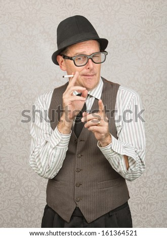 Man in hat and eyeglasses smoking with finger pointing - stock photo