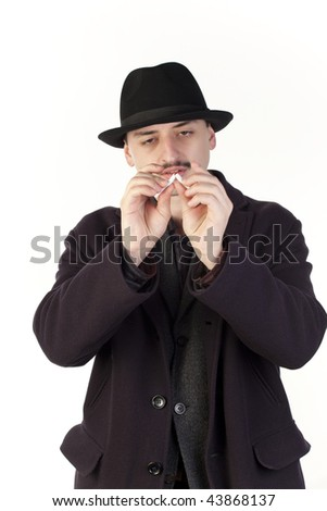 Man in hat breaking a cigarette