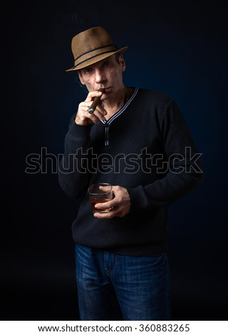 man in hat with cigar and whiskey