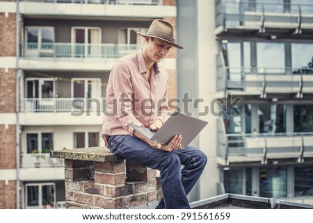Man in hat with laptop. Multifamilly houses on background. - stock photo