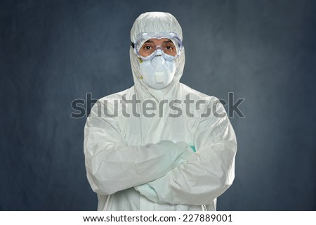 Man in Hazmat suit, protective gloves and goggles inside tent - stock photo