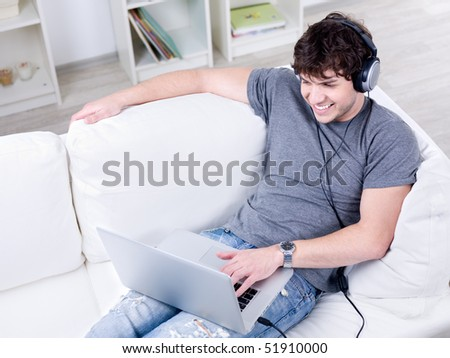 Man in headphone relaxing on the sofa and using laptop - indoors - stock photo