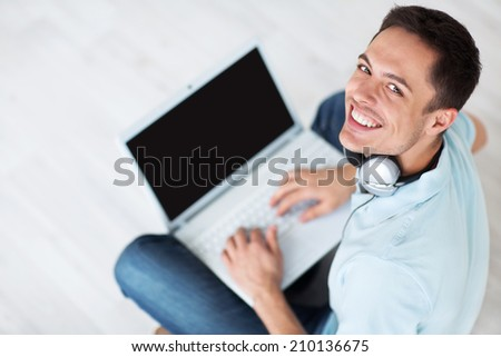 Man in headphones with a laptop - stock photo