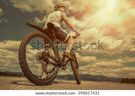 Man in helmet and glasses stay on the bicycle under sky with clouds. - stock photo