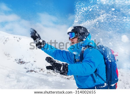 Man in helmet and goggles playing snowballs in the mountains - stock photo