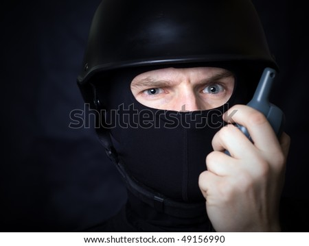 Man in helmet and mask communicate by walkie-talkie radio. Might be a terrorist with bomb detonator - stock photo