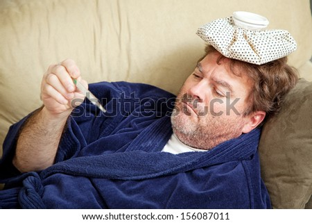Man in his bathrobe on the couch, home sick from work.  He has an icepack on his head and is taking his temperature.