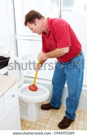 Man in his bathroom unclogging a toilet with a plunger.   - stock photo