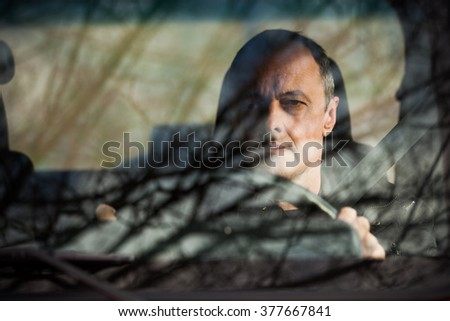 man in his car behind wheel front view through the glass reflection of trees and sky in glass - stock photo