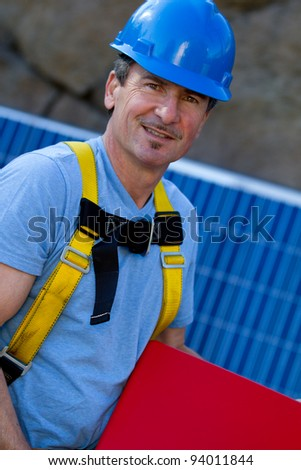Man in his forties overseeing a Solar Installation Holding an Inverter with room for your writting - stock photo