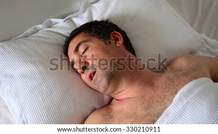 Man in his forties (40s) snoring in bed. Health care concept - stock photo