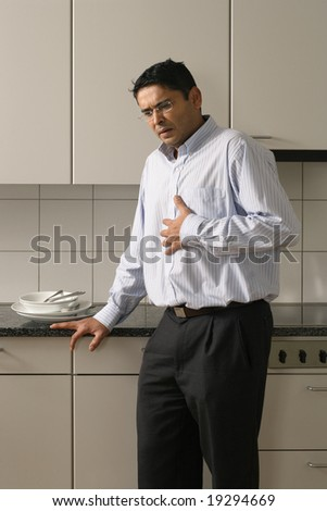 Man in his late thirties standing in his kitchen having a dose of heartburn after a meal. - stock photo